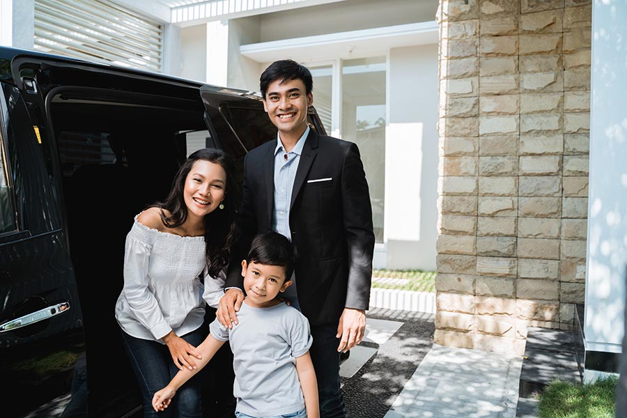 Personal Insurance - Parents and Young Son Standing by Their Black SUV in Front of Their Home