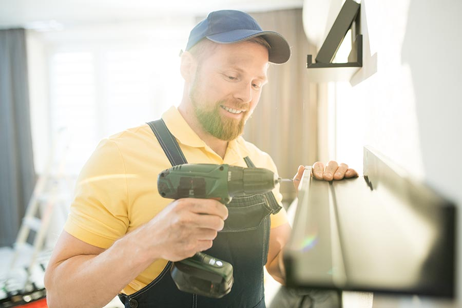 Business Insurance - Contractor Installing Shelving in a Home, Wearing Overalls and a Blue Cap