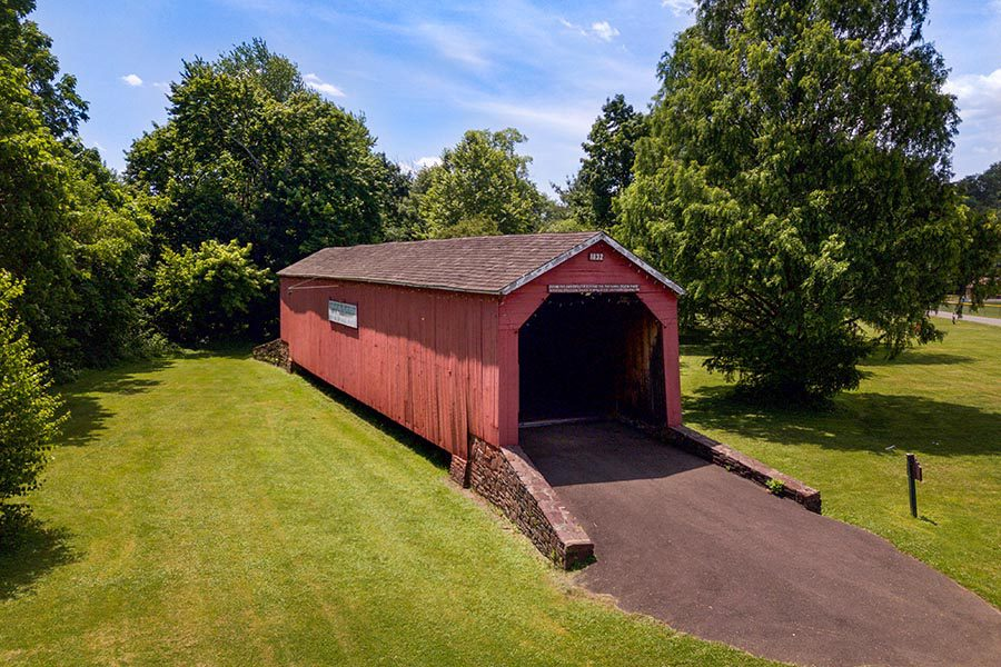 Perkasie, PA Insurance - Red Covered Bridge in Perkasie, Pennsylvania on a Sunny Day, Surrounded by Trees and Green Grass