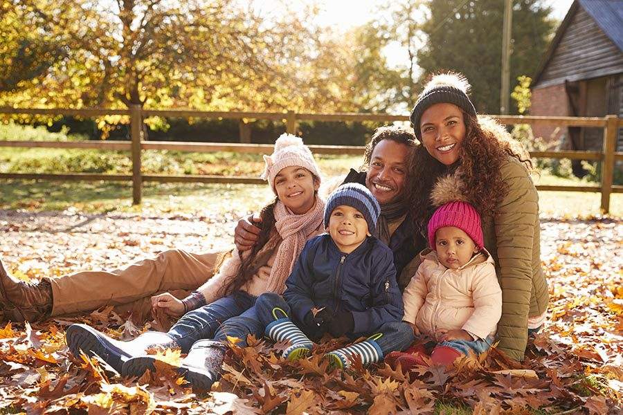 Personal Insurance - Family of Five Sitting in Crisp Fall Leaves in Their Yard, Dressed for Cold Weather