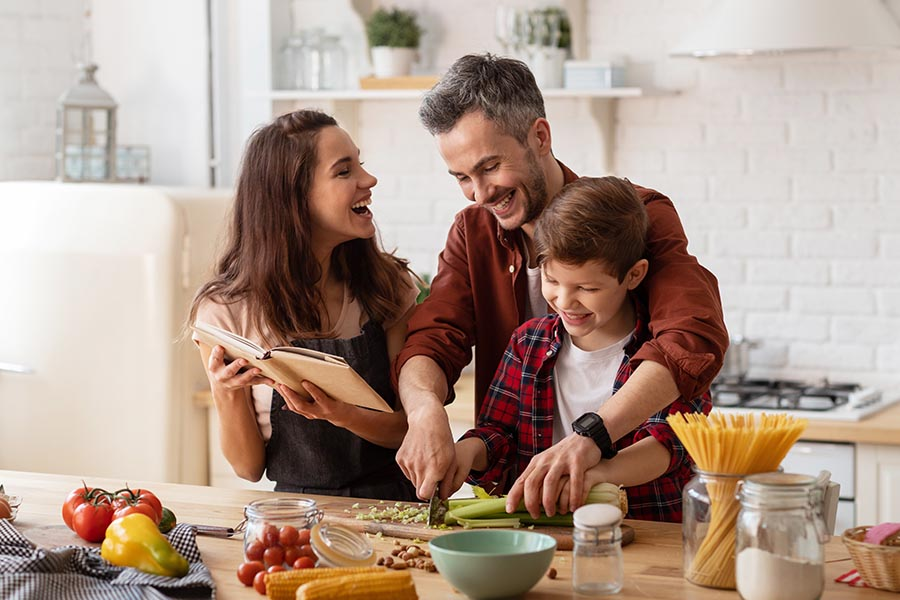 Life and Health Insurance - Family Cooking Dinner Together in Their Kitchen, Laughing and Reading a Recipe Book