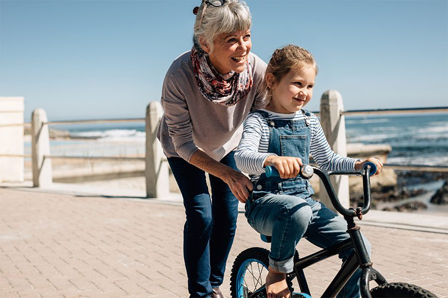 About Our Agency - Portrait of a Cheerful Grandmother Teaching Her Smiling Granddaughter How to Ride a Bike on the Boardwalk