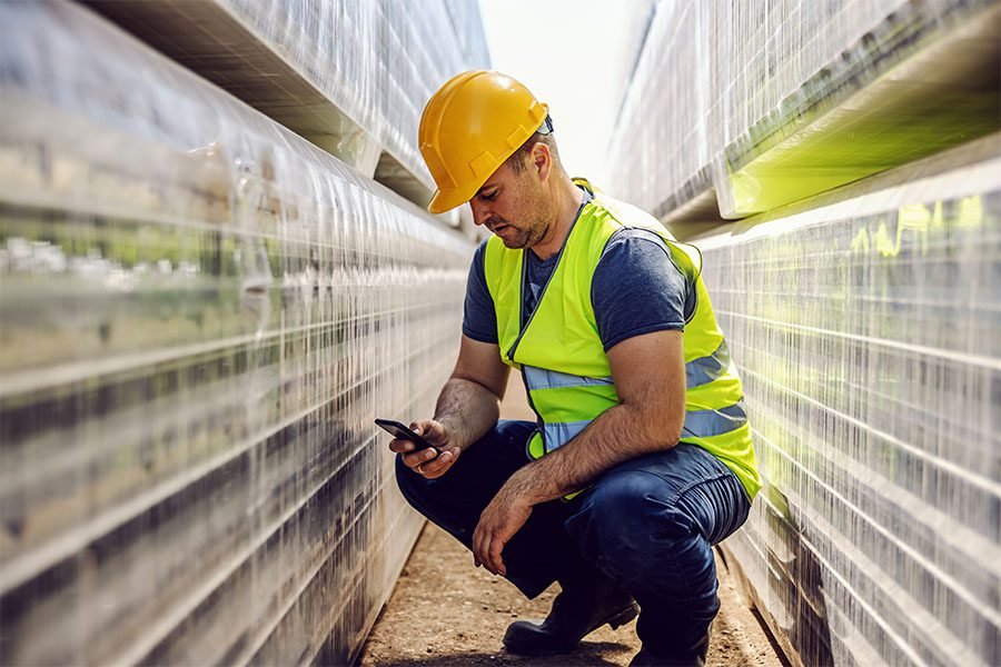 Client Center - Portrait of a Contractor Using a Phone While Crouching in Between Piles of Folded Bricks
