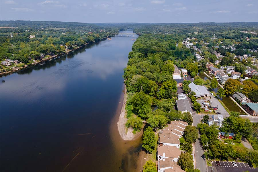 Contact - Scenic View of Homes Next to a River Surrounded by Green Foliage on a Sunny Day in New Jersey