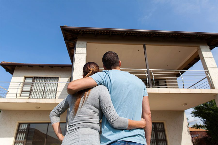 Personal Insurance - Rear View of a Happy Couple Hugging Each Other While Standing Outside and Looking at Their New Home