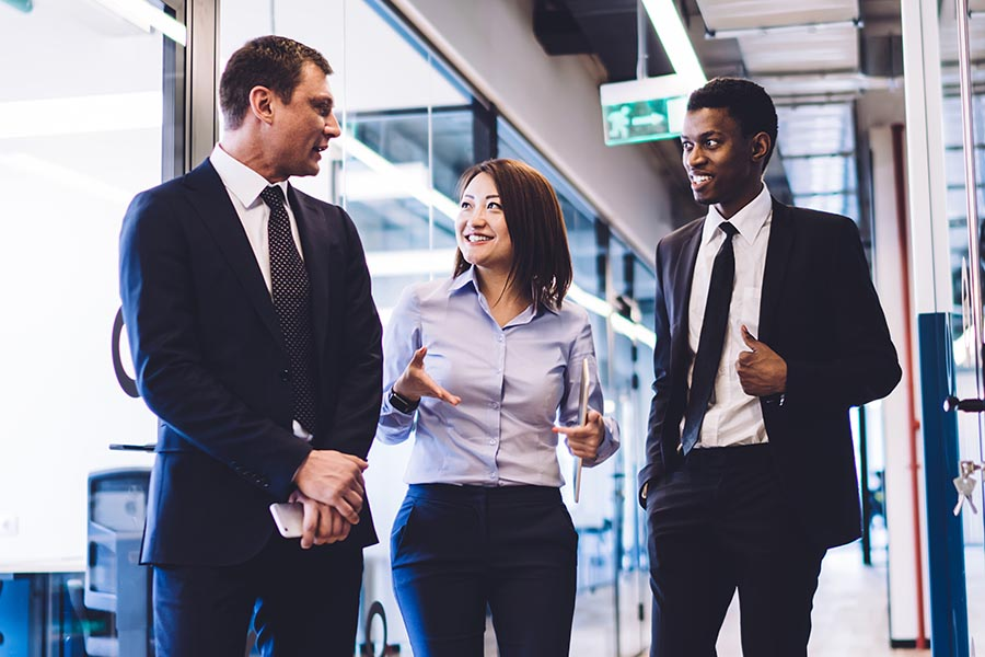 Business Insurance - Three Business Professionals Walk Down a Bright Hallway Smiling