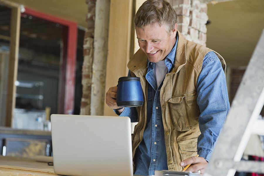 Client Center - Contractor Using a Computer at a Job Site While Drinking Coffee