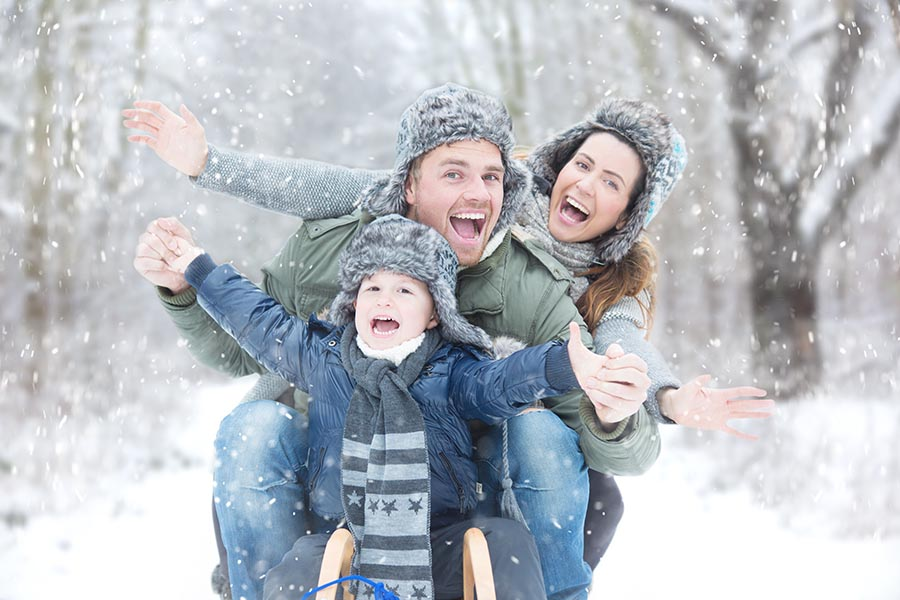Personal Insurance - Family of Three Play in the Snow, Bundled up for the Cold Weather, Smiling Broadly