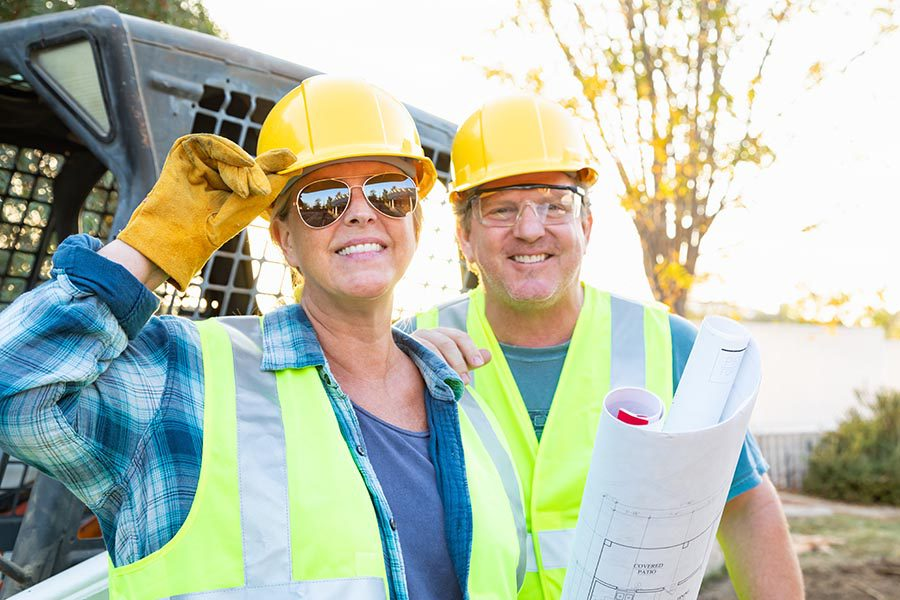 Specialized Business Insurance - Contractors Wearing Reflective Vests and Yellow Hard Hats, Smiling and Holding Blueprints