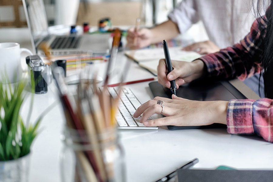 Media and Web Design Insurance - Closeup of a Designer Working at Her Desk and Using a Drawing Tablet