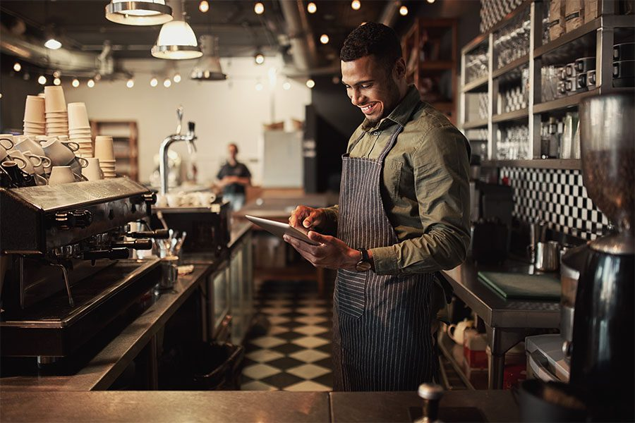 Client Center - Portrait of a Smiling Young Restaurant Owner Standing Behind the Front Counter While Using a Tablet