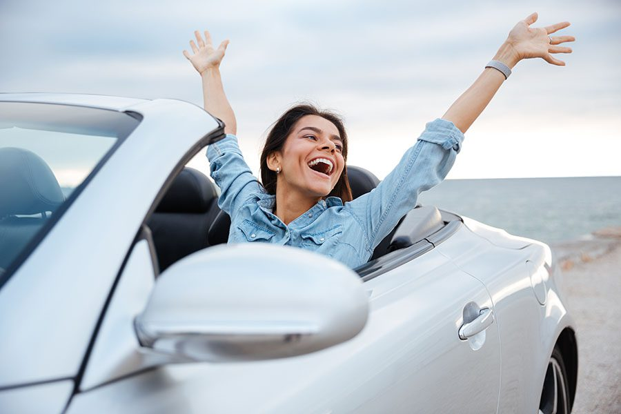 Insurance Quote - Portrait of an Excited Young Woman Sitting in a Convertible Car While on a Road Trip By the Coast