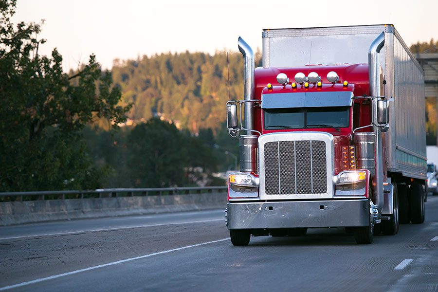 Specialized Business Insurance - Closeup View of a Red Tractor Trailer Truck Driving on the Highway with Views of the Mountains in the Background