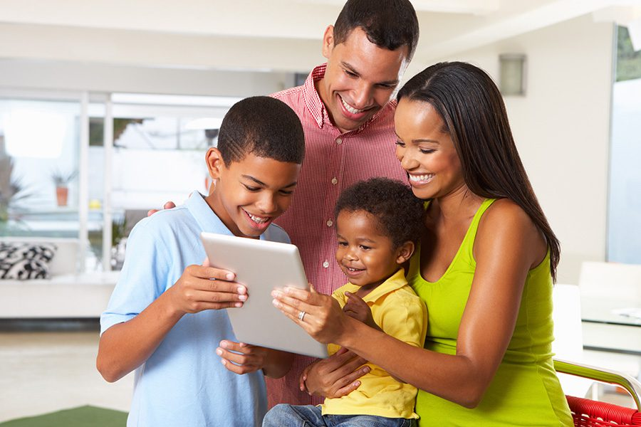 Client Center - Happy Family Using a Tablet in Their Kitchen Together at Home