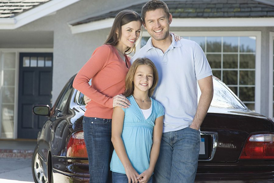Personal Insurance - Portrait of a Happy Couple With Their Daughter Standing Against Their Car and House