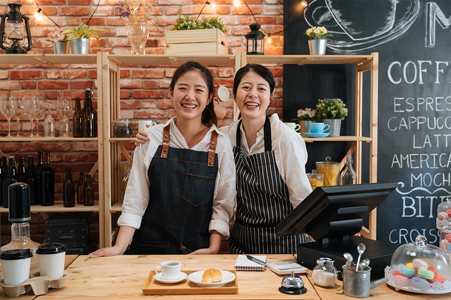 Business Insurance - Two Women Running a Cafe, Smiling and Wearing Aprons