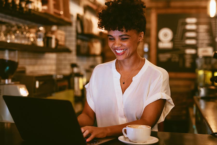 Client Center - Young Woman Grinning as She Uses a Laptop in a Dimly Lit Cafe, a Cappuccino on Her Table