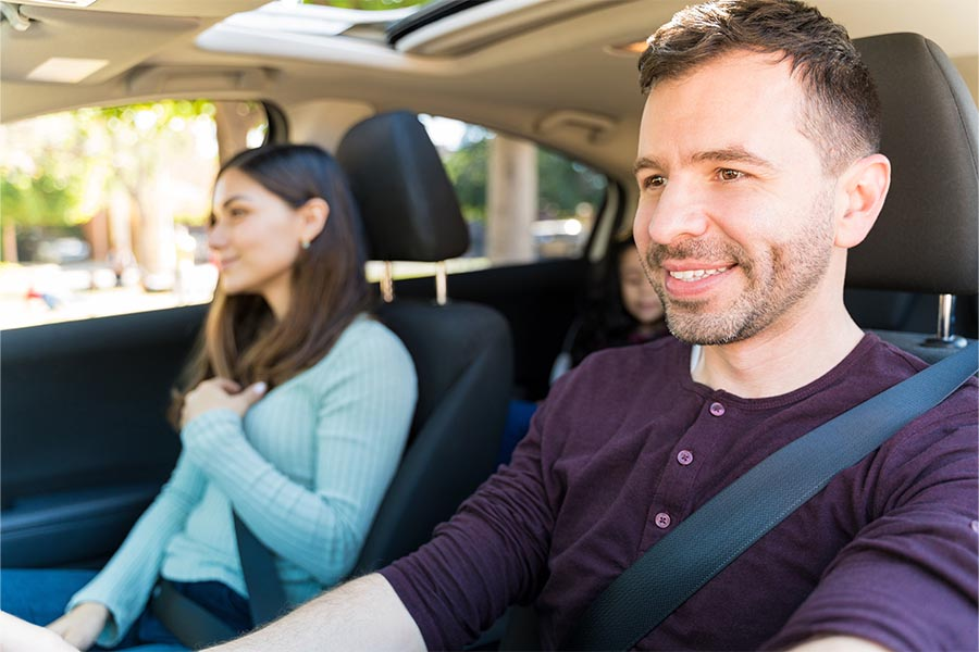 Personal Insurance - A Couple Driving in Their Car, Young Daughter in the Backseat, Husband at the Wheel