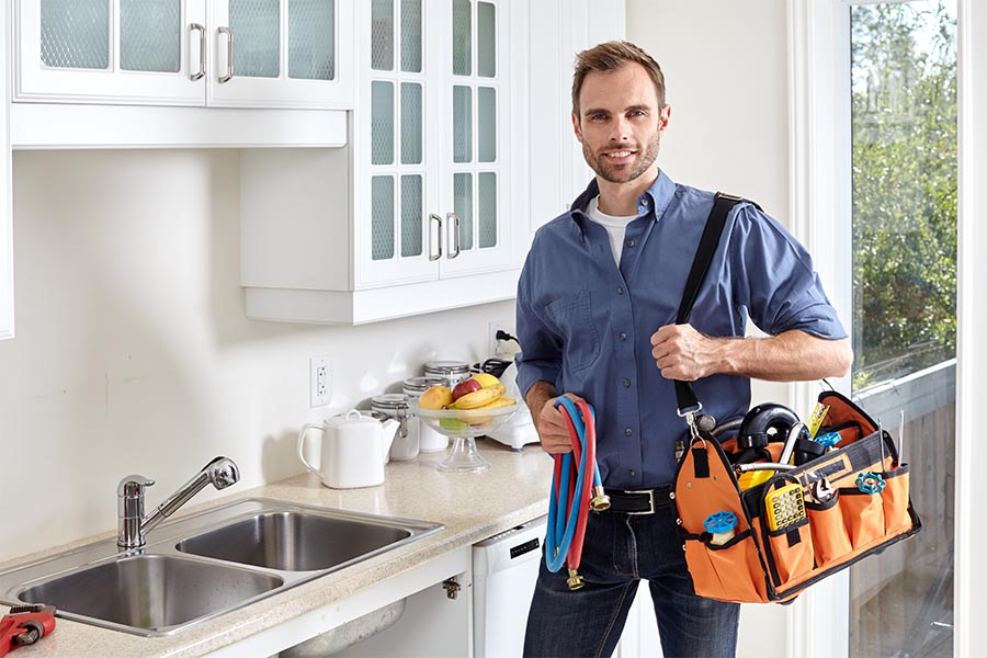 Specialized Business Insurance - Contractor Holding a Tool Caddy, Pipes, and Standing by a Kitchen Sink