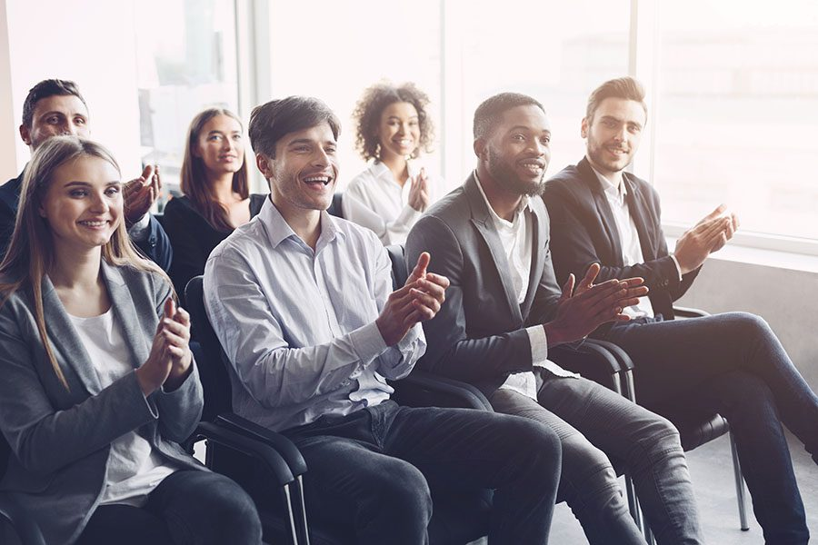 Blog - Portrait of a Group of Smiling Employees Clapping Their Hands While Sitting in a Conference Meeting in the Office