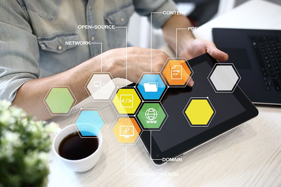 CMS Templates - Closeup View of a Man Sittiing at a Wooden Desk with a Coffee While Using a Tablet with Colorful Projections of Business and Technology Concepts