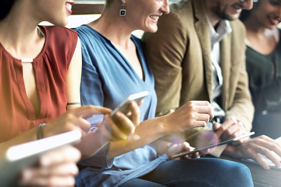 Customize List Templates - View of a Group of Cheerful Business Employees Sittiing in a Row in the Office Using Their Phones and Tablets