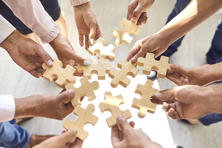 Partners - Closeup View of a Group of Business Professionals Holding Out Wooden Puzzle Pieces in Their Hands in a Huddle