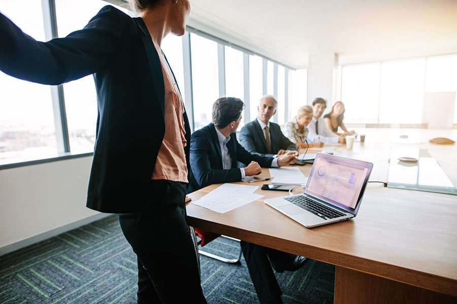 Proposal Templates - View of a Woman Giving a PowerPoint Presentation to Her Peers During a Business Meeting in a Modern Office