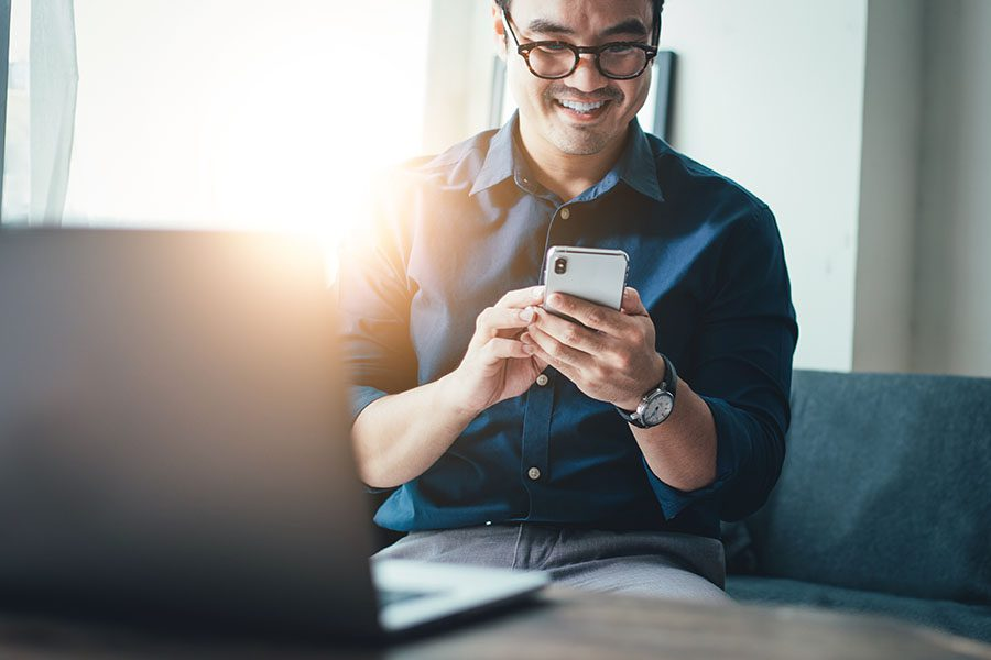Text Message Templates - Portrait of a Cheerful Man Wearing Glasses Sitting on the Sofa While Using a Phone with a Laptop on the Coffee Table Next to Him