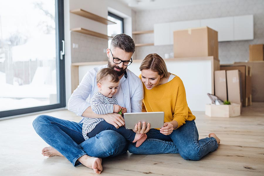 Client Center - Parents and Baby Sit On the Floor of Their Living Room Using a Tablet