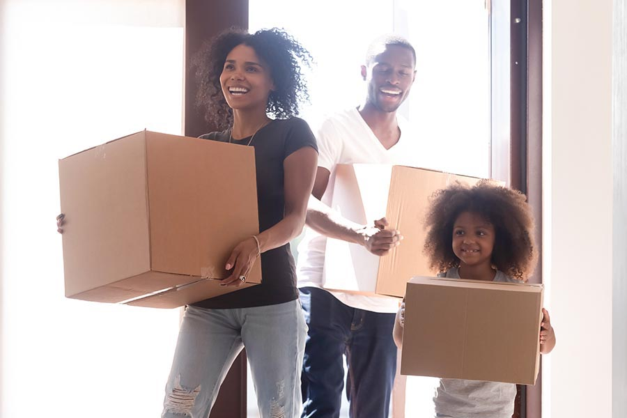 Personal Insurance - Happy Family Running into Their New Home Carrying Cardboard Boxes