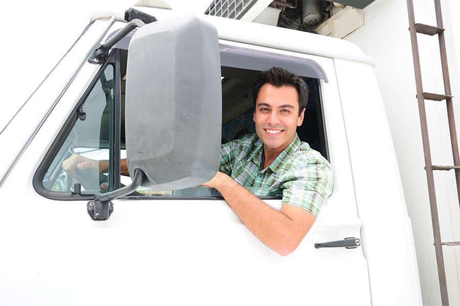 Specialized Business Insurance - Truck Driver Smiles and Leans Out the Window of the Cab of His White Truck