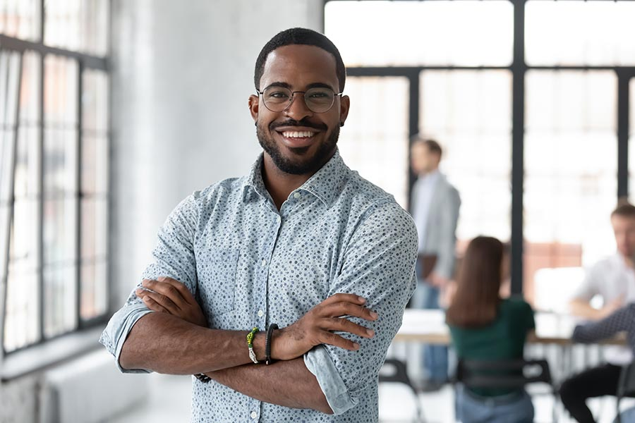 Business Insurance - Smiling Young Business Owner Stands With Arms Crossed In a Large Modern Office