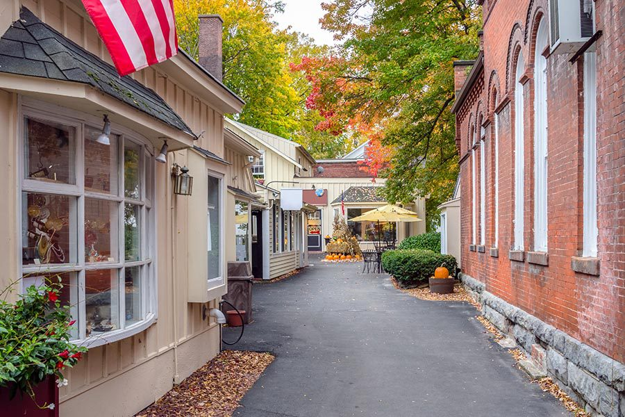 Homepage - Shops in Virginia With Glass Display Windows and Brick Facades, Leaves and Pumpkins Lining the Road