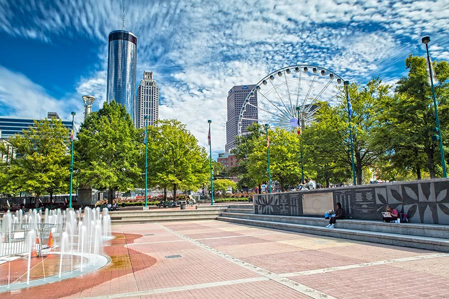 About Our Agency - Fountain and Walking Path in Atlanta, Georgia Olympic Centennial Park, the Skyline and Ferris Wheel in the Background