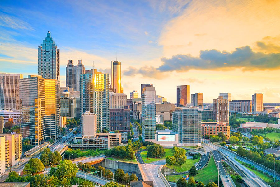 Contact - Aerial View of an Atlanta City Skyline Displaying Many Tall Buildings and Parks During Sunrise