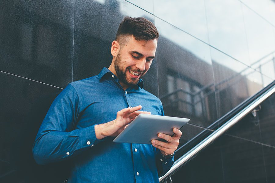 Blog - Closeup Portrait of a Cheerful Young Man Wearing a Dress Shirt Standing Outside While Using a Tablet