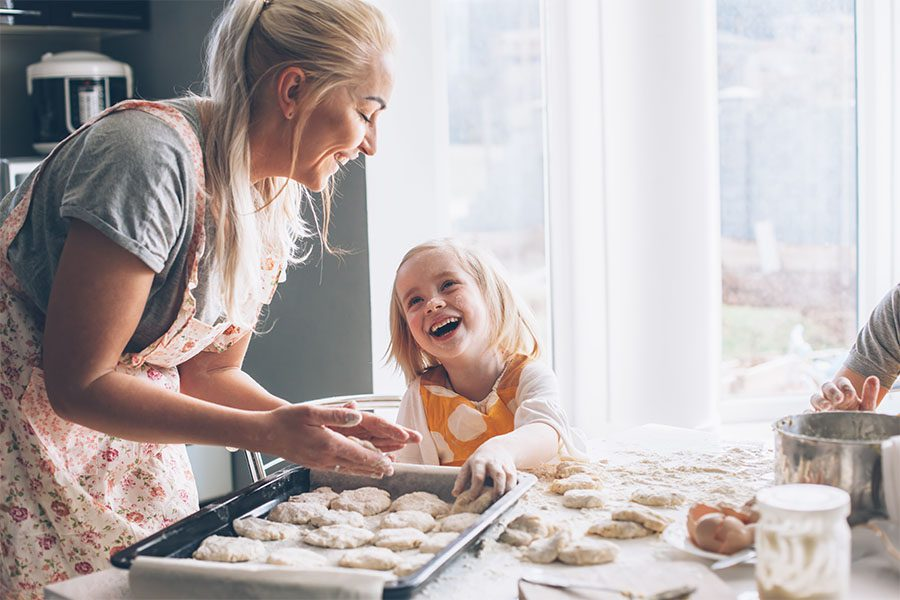 Client Center - View of a Cheerful Grandmother and Granddaughter Having Fun Together While Cooking Together in the Kitchen