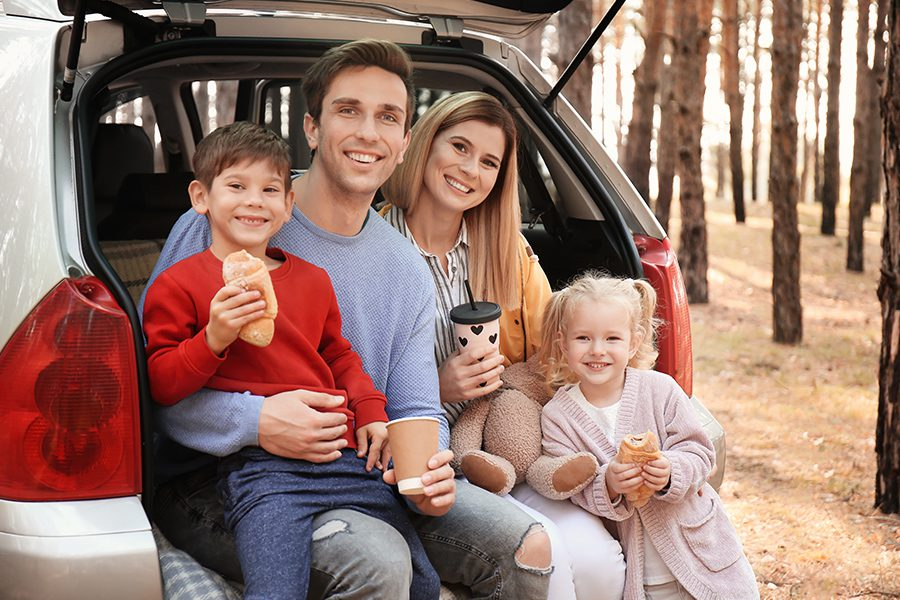Personal Insurance - Young Couple with Their Young Children Having Lunch While Sitting in the Back of the Car
