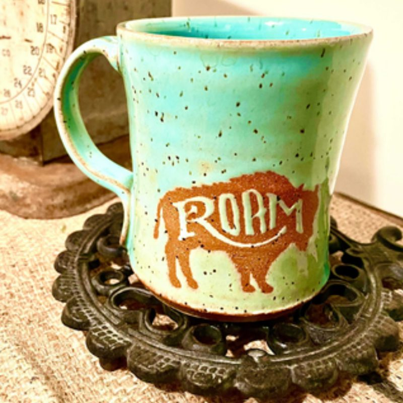 Favorite Beverage - Mug Image of Buffalo and the Word Roam on Coaster Next to a Scale