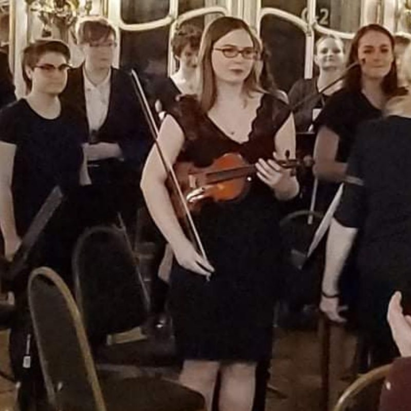 Hidden Talents - Becky With a Violin and Bow Surrounded by People and Chairs