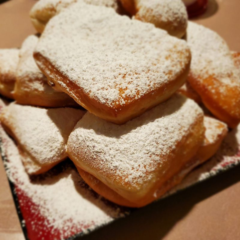 Hidden Talents - Beignets Stacked on a Plate Covered in Powdered Sugar