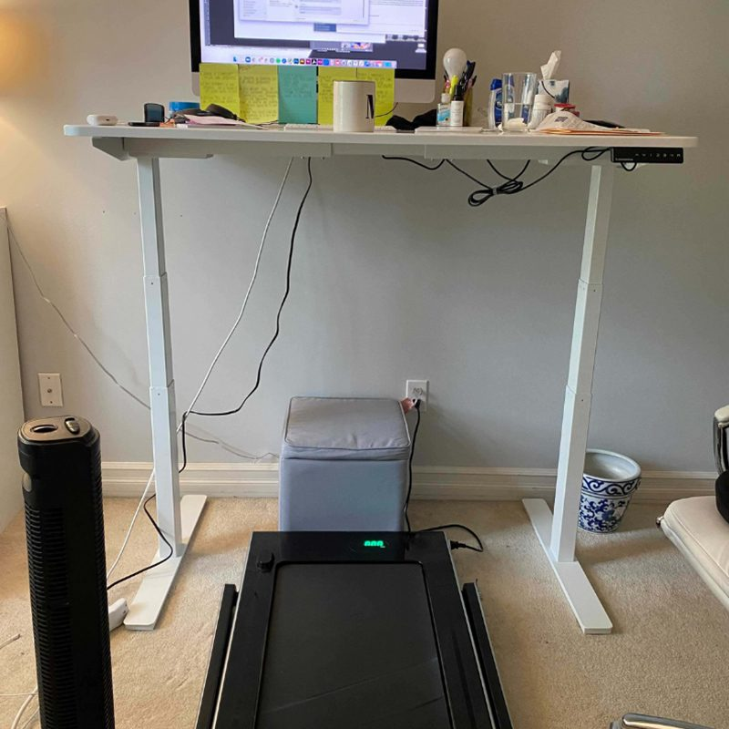 Hidden Talents - Computer and Papers on Desk With Treadmill