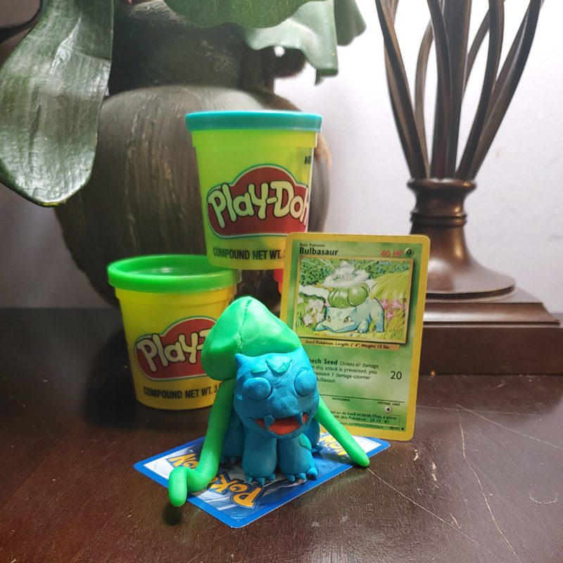 Hidden Talents - Containers of Play-Doh Stacked Next to Pokemon Card and Sculpture