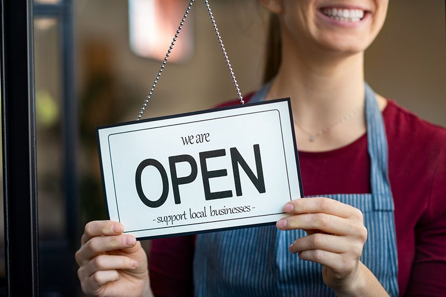 Business Insurance - Smiling Small Business Owner Holding Up Open Sign on Front Door