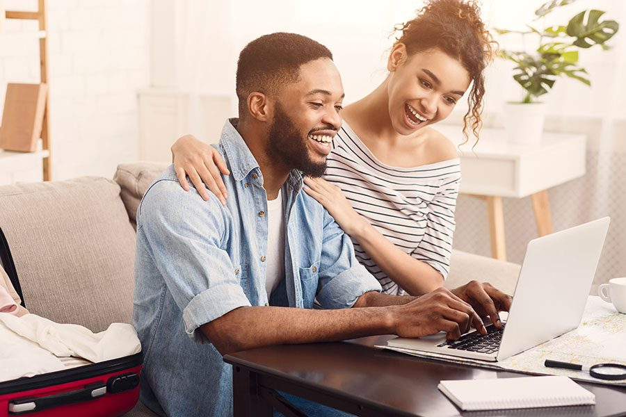 Client Center - Happy Couple Sitting at Home Using a Laptop