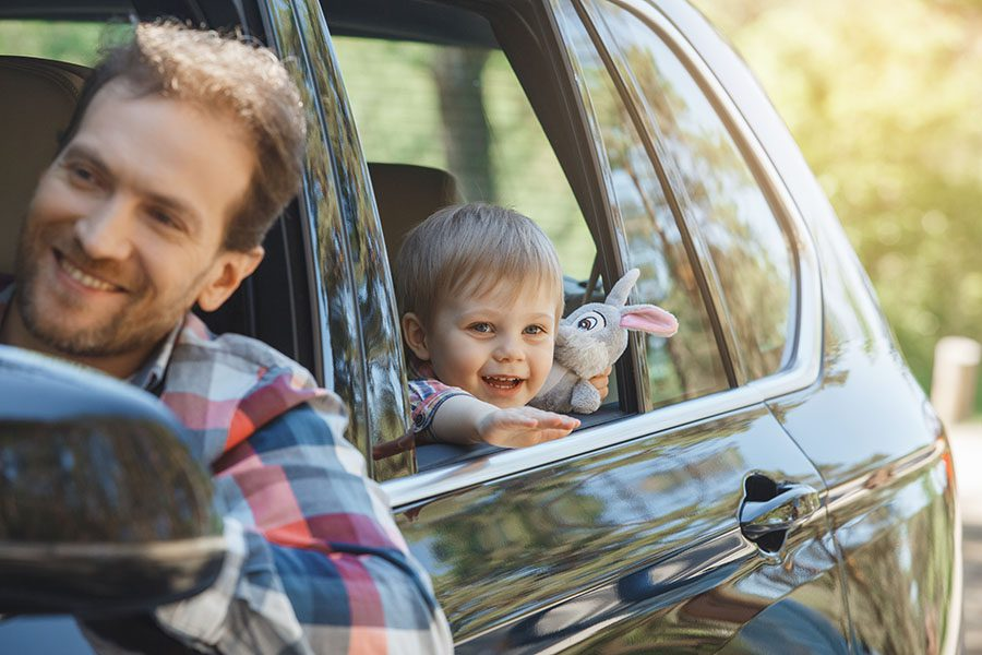 Contact - Smiling Father and Son Driving in the Car on Road Trip