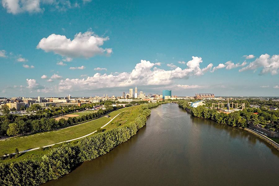 About Our Agency - Indianapolis Skyline in the Distance, River and Green Fields in the Foreground, White Clouds Above in a Bright Blue Sky
