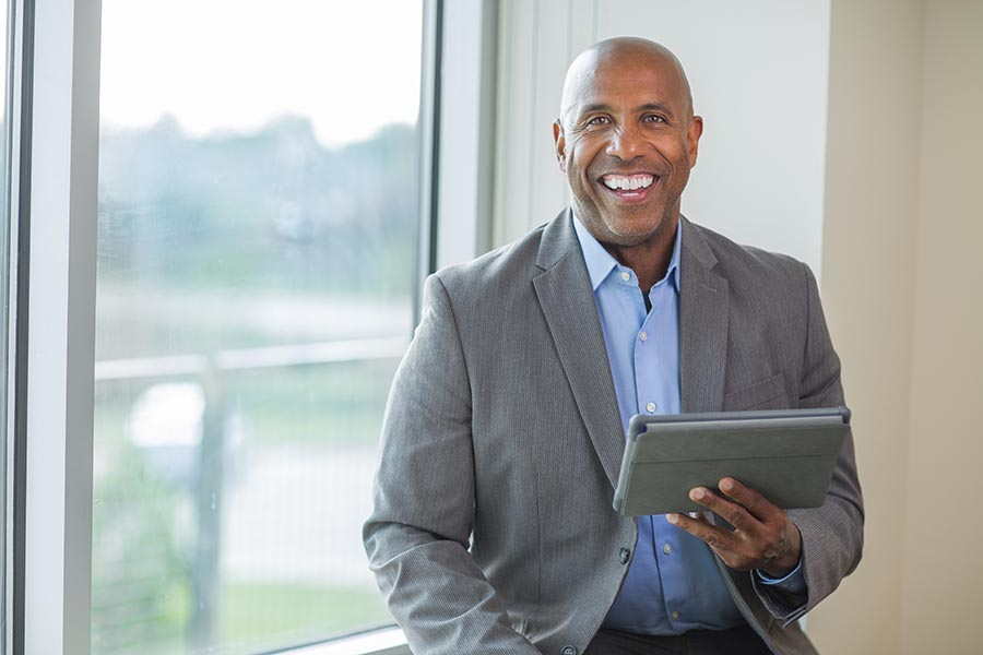 Blog - Businessman Smiles as He Uses a Tablet by a Window in an Office Building