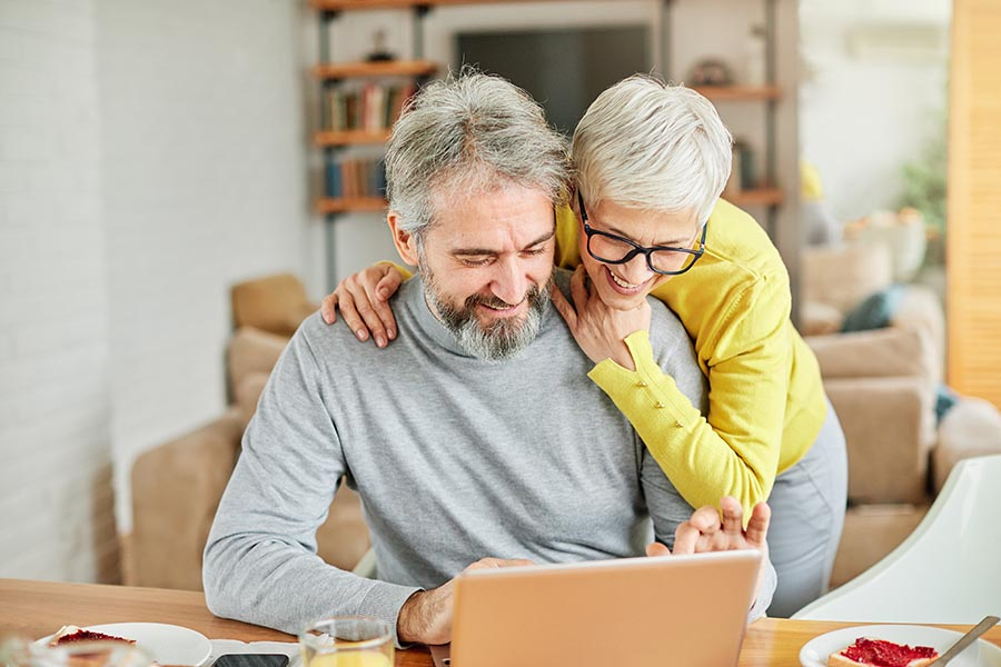 Client Center - Senior Couple Use a Computer in Their Bright Home at the Kitchen Table, Wife Wrapping Her Arms Around Husband